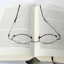 Photo: pair of glasses on an open book